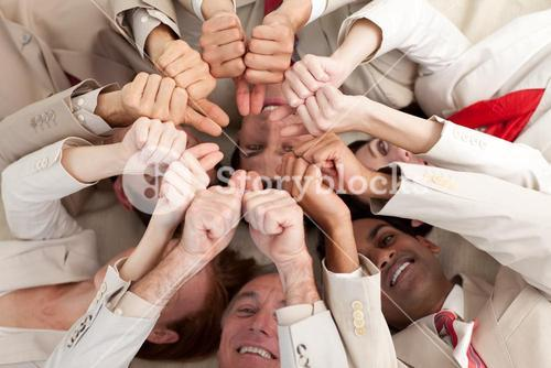Smiling business people with thumbs up lying on the floor