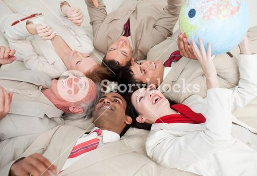 Business team lying on the floor playing with a terrestrial globe