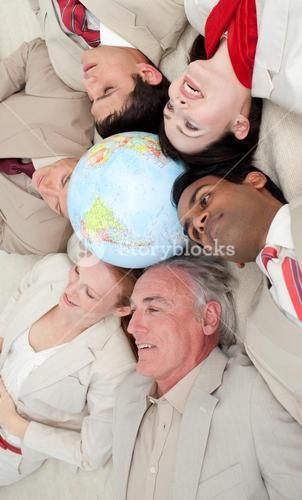 Business team lying on the floor around a terrestrial globe