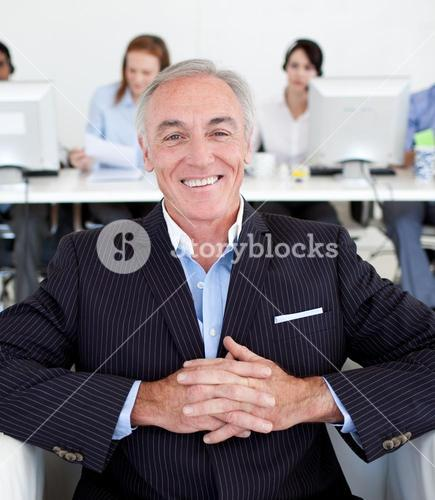 Smiling senior manager with his team in the background