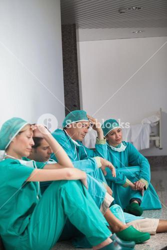Team of exhausted surgeons sitting on the floor
