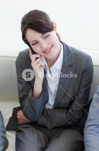 Smiling businesswoman on phone while waiting for a job interview