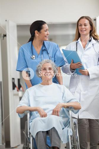 Nurse wheeling a patient in a hallway