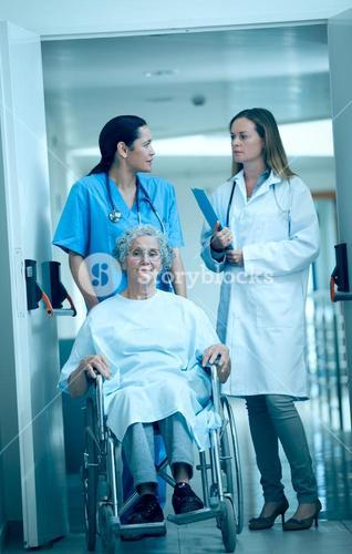Nurse wheeling a senior patient patient in a hallway