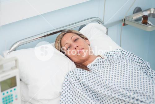 Woman lying on a bed while looking at camera