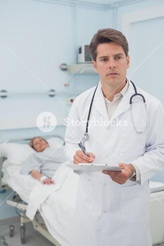 Thoughtful doctor writing on a clipboard
