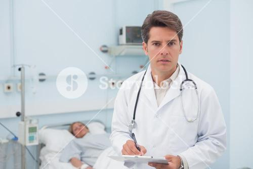 Doctor writing while holding a chart