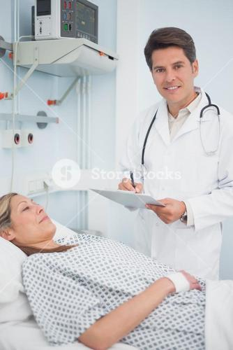 Doctor writing on his clipboard next to his patient
