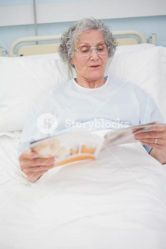 Patient reading a magazine on her bed