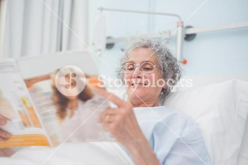 Elderly patient reading a magazine on her bed