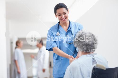 Nurse standing next to a patient while holding her hands