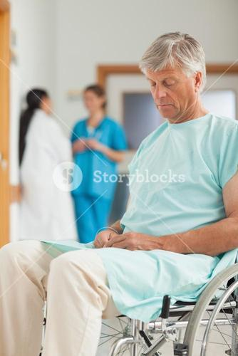 Male patient in a wheelchair next to nurses