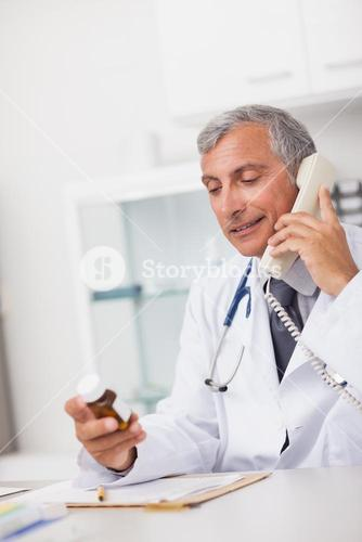 Doctor holding a drug box and a phone