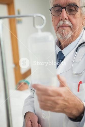 Doctor checking an intravenous drip