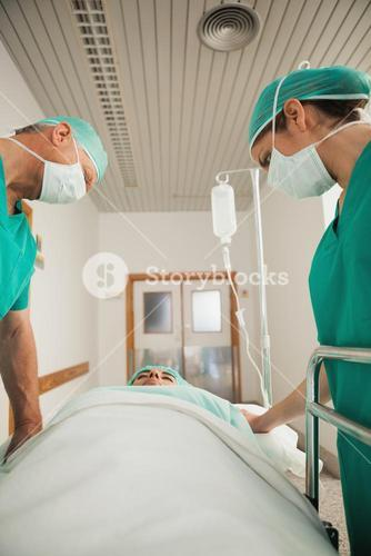 Surgeons looking at a patient asleep