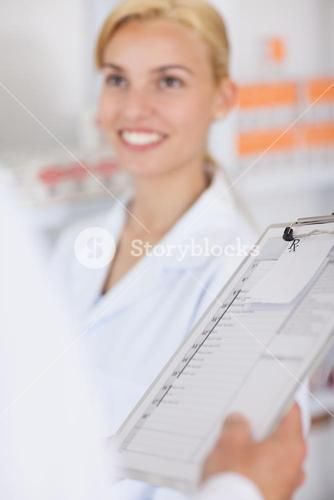 Blonde pharmacist smiling to someone
