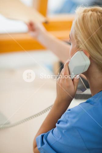 Nurse holding a phone and giving a folder