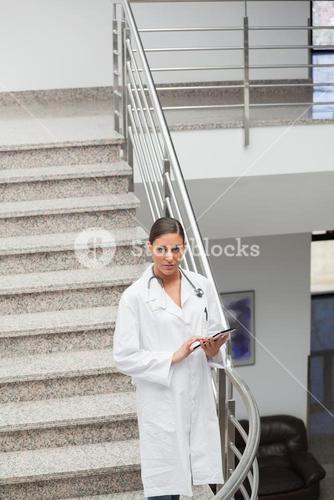 Front view of a doctor touching a tablet computer