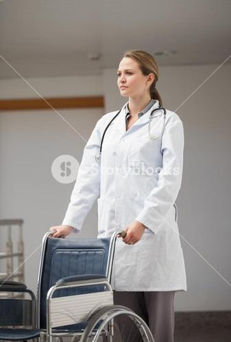 Serious female doctor pushing a wheelchair