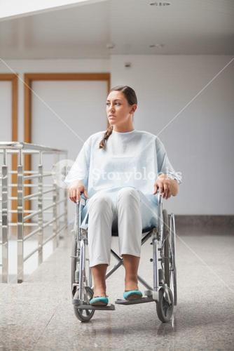 Front view of a thoughtful patient sitting on a wheelchair
