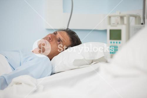Thoughtful patient lying on a medical bed