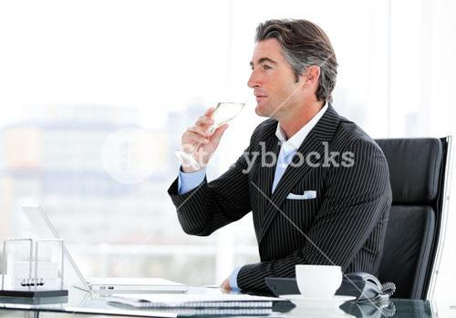 Charismatic businessman drinking a glass of water