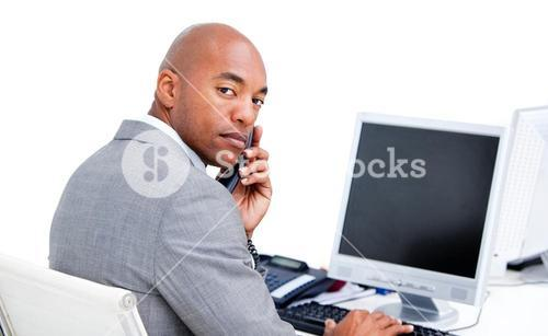 Positive businessman on phone at his desk