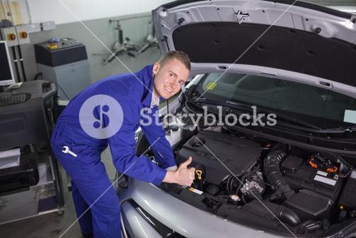 Smiling mechanic leaning on a car with his thumb up