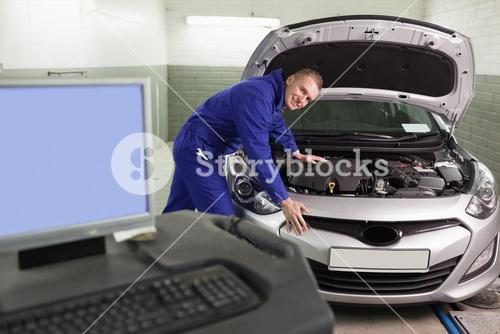 Mechanic leaning on a car next to a computer