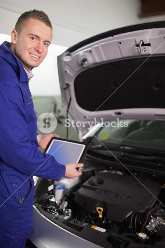Smiling mechanic testing an engine with a tablet computer