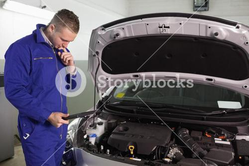 Concentrated mechanic looking at a tablet computer