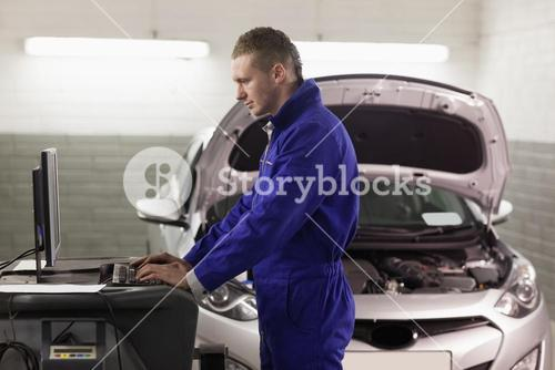 Concentrated mechanic looking at a computer