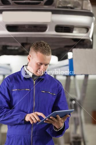 Concentrated mechanic holding a tablet computer