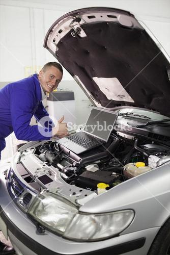 Mechanic repairing a car with a computer