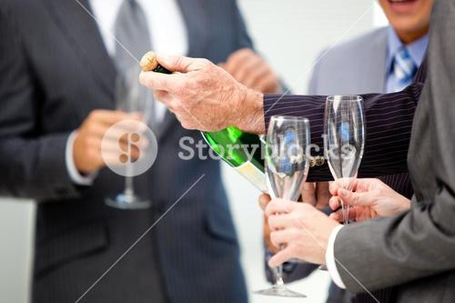 Close up of a business man opening a bottle of Champagne