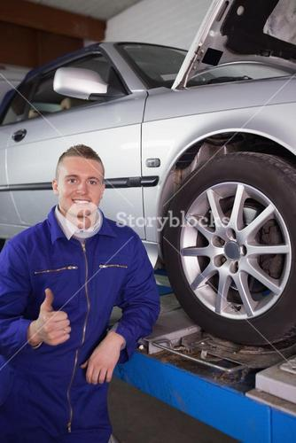 Man smiling next to a car with his thumb up