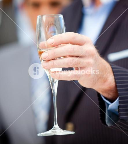 Close up of a businessman holding a glass of Champagne