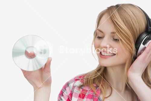 Woman holding a cd while listening music