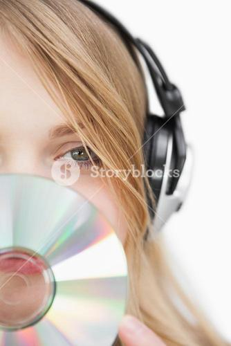 Close up of a blonde woman with a cd in front of her face