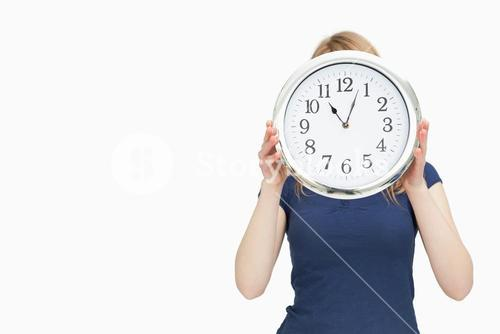 Blonde woman holding a clock
