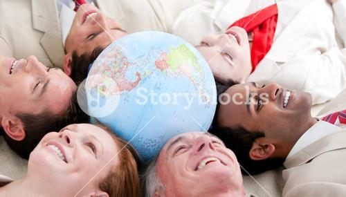 Business people lying around a globe
