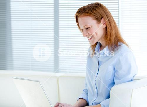 Happy business woman working on a laptop computer