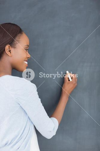 Black woman writing on a blackboard