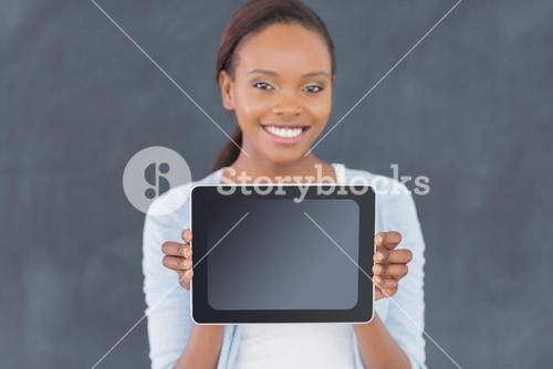 Black woman holding a tablet computer next to a blackboard