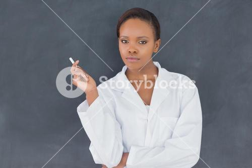 Teacher holding a chalk while looking at camera