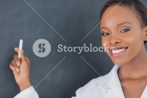 Teacher smiling while holding a chalk