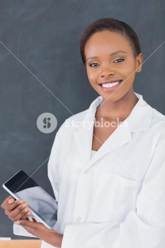 Teacher holding a tablet computer while looking at camera