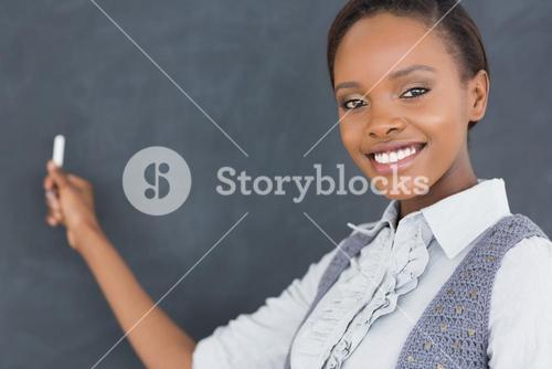 Black teacher looking at camera while holding a chalk
