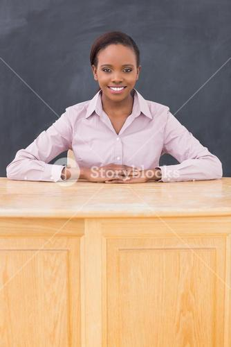 Teacher smiling while sitting at her desk