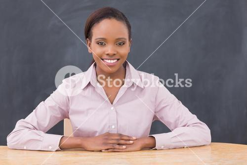 Teacher smiling while putting her hands on desk